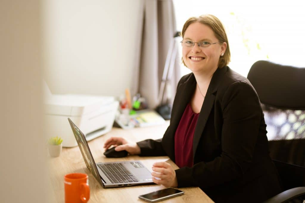 Sonja Kloos am Schreibtisch bei der Arbeit, lächelnd